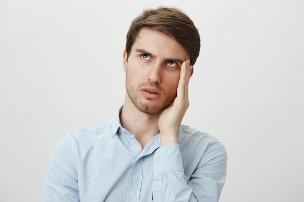 Раздраженный парень закатывает глаза и раздражает фейспалм