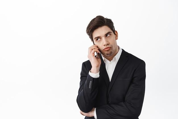 Раздраженный парень разговаривает по телефону и закатывает глаза, устал от скучного разговора, скучный человек по вызову, стоит в черном костюме у белой стены