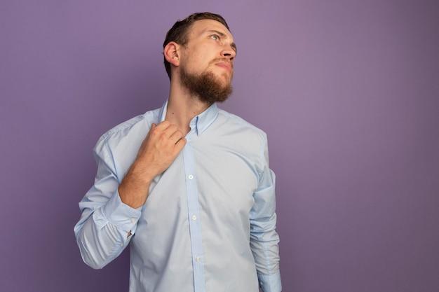 Uomo biondo bello infastidito tiene il collare e guarda il lato isolato sulla parete viola