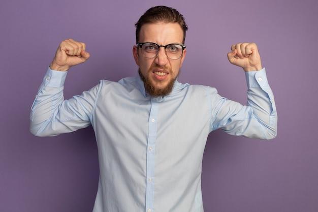 광학 안경에 짜증이 잘 생긴 금발의 남자가 보라색 벽에 고립 된 주먹을 유지
