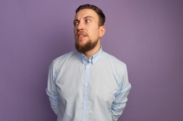 Uomo biondo bello infastidito guarda al lato isolato sulla parete viola