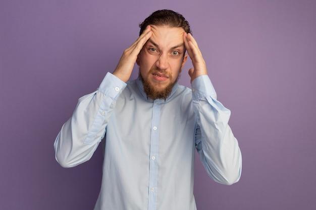 짜증이 잘 생긴 금발의 남자가 보라색 벽에 고립 된 이마에 손을 넣습니다.