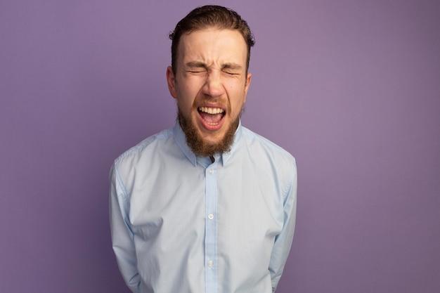 Uomo biondo bello infastidito urla con gli occhi chiusi isolati sulla parete viola
