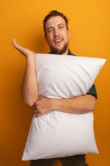 Uomo biondo bello infastidito sta con la mano alzata e tiene il cuscino isolato sulla parete arancione