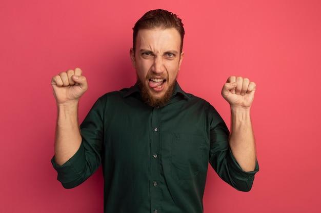 짜증이 잘 생긴 금발의 남자가 혀를 찌르고 분홍색 벽에 고립 된 주먹을 들고 서 있습니다.