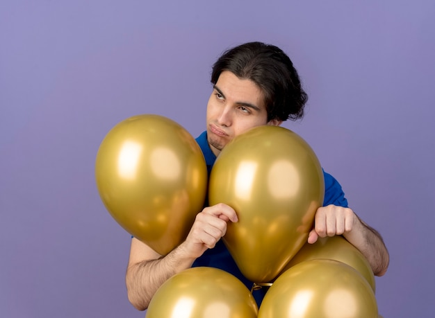 Annoyed handsome caucasian man stands with helium balloons looking at side
