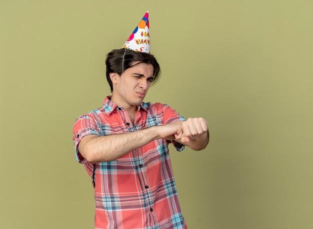 Un bell'uomo caucasico infastidito che indossa un berretto da compleanno tiene e guarda a portata di mano