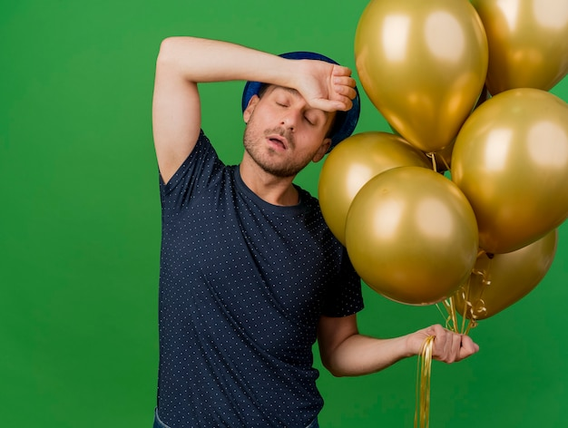 Annoyed handsome caucasian man wearing blue party hat holds helium balloons and puts hand on forehead isolated on green background with copy space