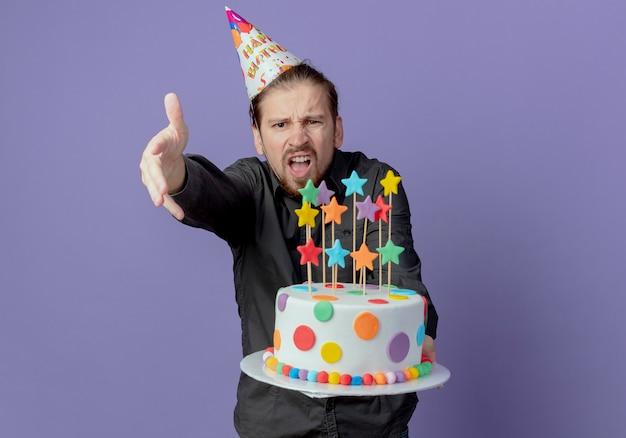Uomo bello infastidito in protezione di compleanno tiene la torta e indica in avanti con la mano isolata sulla parete viola