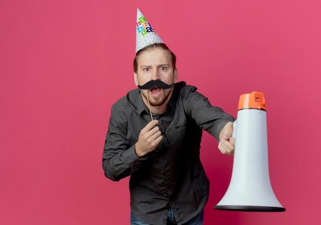 Uomo bello infastidito in protezione di compleanno tiene altoparlante e baffi finti sul bastone isolato sulla parete rosa