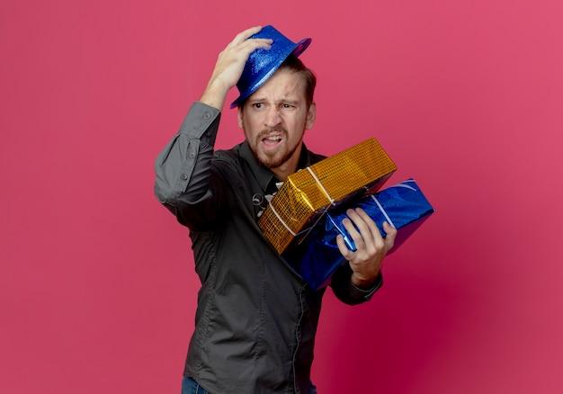 Uomo bello infastidito in cappello blu si leva in piedi lateralmente tenendo i contenitori di regalo isolati sulla parete rosa