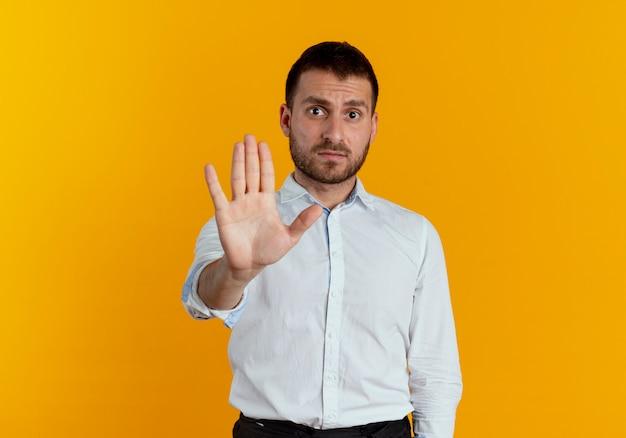 Gesti di uomo bello infastidito stop mano segno isolato sulla parete arancione