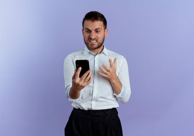 L'uomo bello infastidito tiene e guarda il telefono isolato sulla parete viola