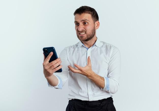 L'uomo bello infastidito tiene ed esamina il telefono che solleva la mano isolata sulla parete bianca