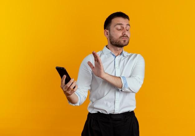 Раздраженный красавец держит экран закрытия телефона с рукой, изолированной на оранжевой стене