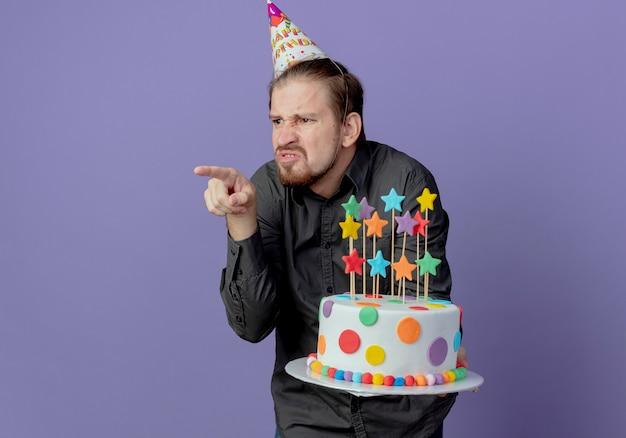 생일 모자에 짜증이 잘 생긴 남자는 보라색 벽에 고립 된 측면에서 케이크와 포인트를 보유
