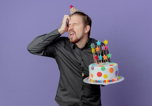 생일 모자에 짜증이 잘 생긴 남자가 이마에 손을 올려 보라색 벽에 고립 된 케이크를 보유하고 있습니다.