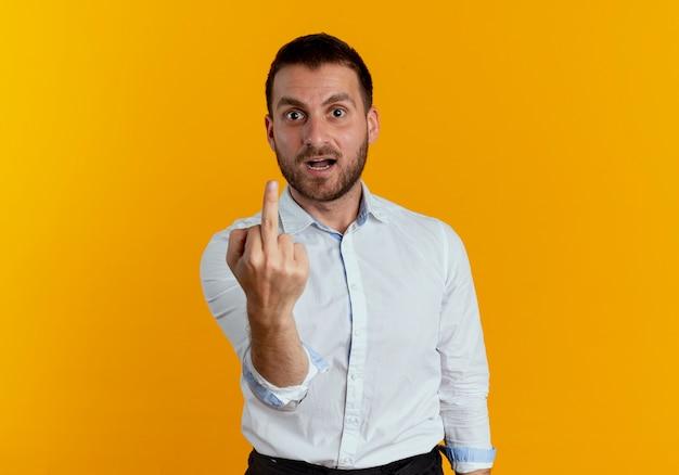 L'uomo bello infastidito mostra il dito medio isolato sulla parete arancione