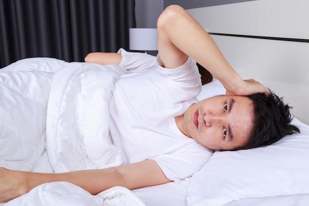寝室でいびきをする妻の騒音から耳を塞いでいる迷惑な夫