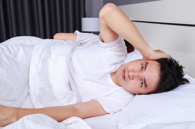 Annoyed husband blocking his ears from noise of wife snoring in bedroom