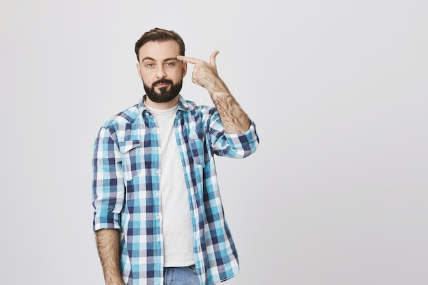 Annoyed and indifferent man make finger gun, shooting himself from boredom