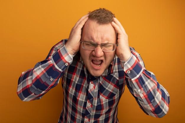 Uomo infastidito e irritato con gli occhiali e la camicia a quadri gridando e urlando con le mani sulla testa in piedi sopra il muro arancione