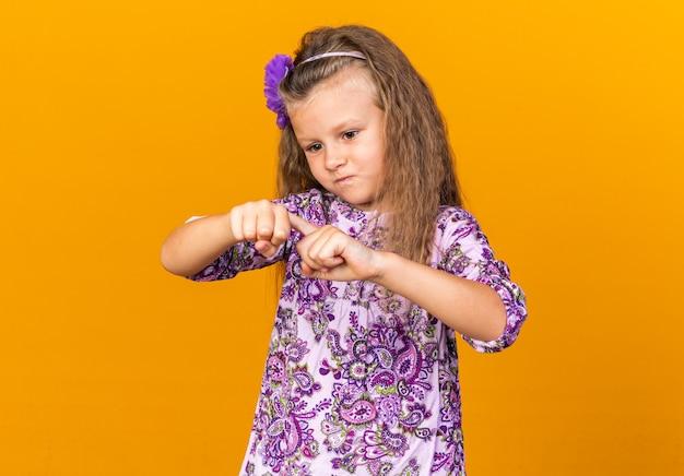 Piccola ragazza bionda infastidita che mette il dito sulla mano e guarda isolata sulla parete arancione con spazio di copia