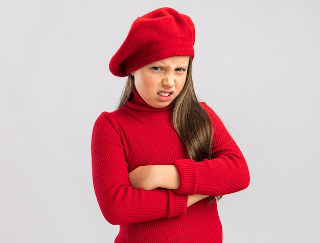 Annoyed little blonde girl wearing red beret keeping arms crossed looking at front isolated on white wall with copy space