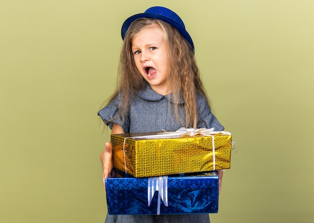 Annoyed little blonde girl with blue party hat holding gift boxes isolated on olive green wall with copy space