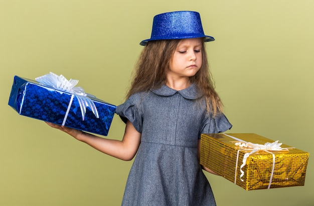 Annoyed little blonde girl with blue party hat holding and looking at gift boxes isolated on olive green wall with copy space