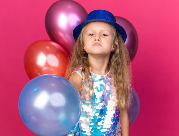 Infastidita bambina bionda con cappello da festa blu in piedi con palloncini di elio isolati sulla parete rosa con spazio di copia
