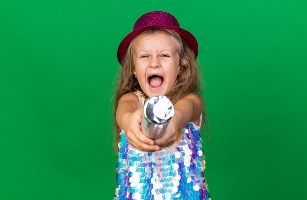 Annoyed little blonde girl with purple party hat holding confetti cannon isolated on green wall with copy space