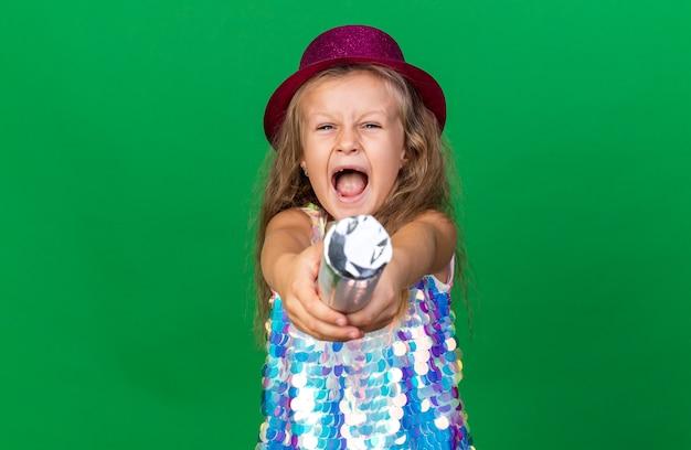 コピースペースで緑の壁に分離された紙吹雪の大砲を保持している紫色のパーティハットでイライラする小さなブロンドの女の子