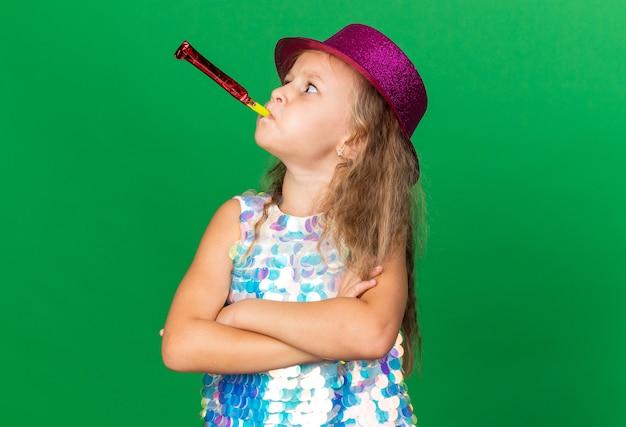 Раздраженная маленькая блондинка в фиолетовой шляпе, стоящая со скрещенными руками, дует в свисток и смотрит в сторону, изолированную на зеленой стене с копией пространства