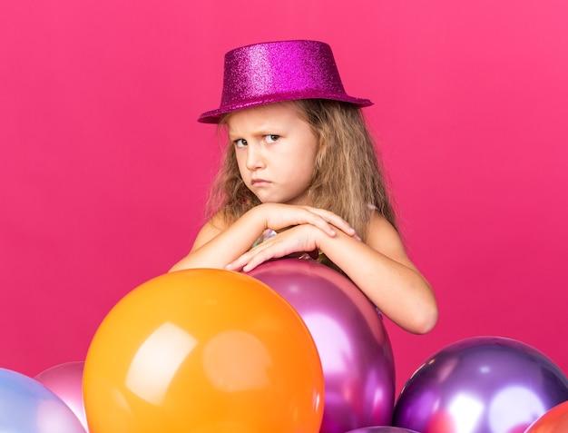 有站立与氦气气球的紫色党帽子的懊恼小白肤金发的女孩隔绝在有拷贝空间的桃红色墙壁