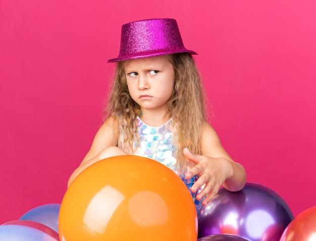 Infastidita bambina bionda con cappello da festa viola in piedi con palloncini di elio e guardando il lato isolato sul muro rosa con spazio di copia