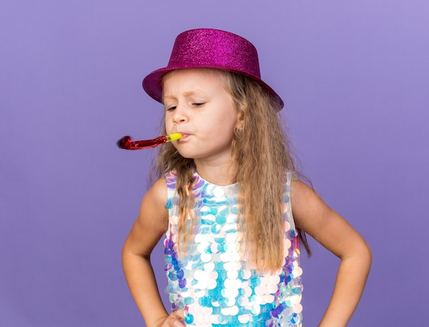 Annoyed little blonde girl with violet party hat blowing and looking at party whistle isolated on purple wall with copy space