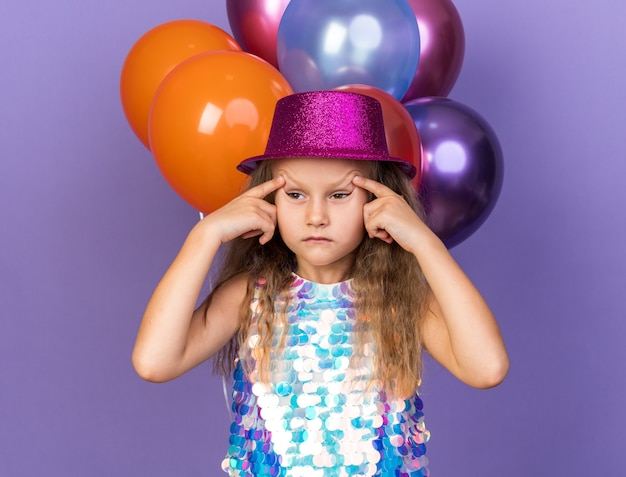 Annoyed little blonde girl with violet party hat raising eyebrows with fingers standing in front of helium balloons isolated on purple wall with copy space