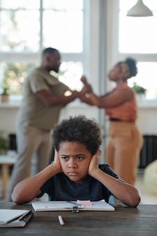 Раздраженный маленький мальчик, закрывая уши руками, сидя за столом и пытаясь выполнить школьное задание, несмотря на то, что его родители гуляли