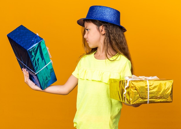 파란색 파티 모자를 들고 복사 공간이 오렌지 벽에 고립 된 선물 상자를보고 짜증이 어린 백인 소녀