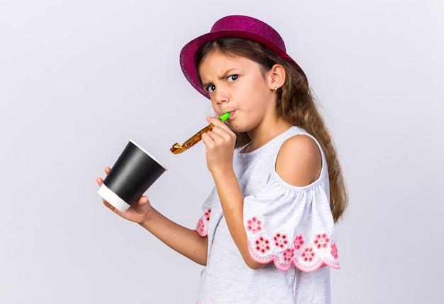 Раздраженная маленькая кавказская девушка с фиолетовой шляпой дует свисток и держит бумажный стаканчик на белой стене с копией пространства