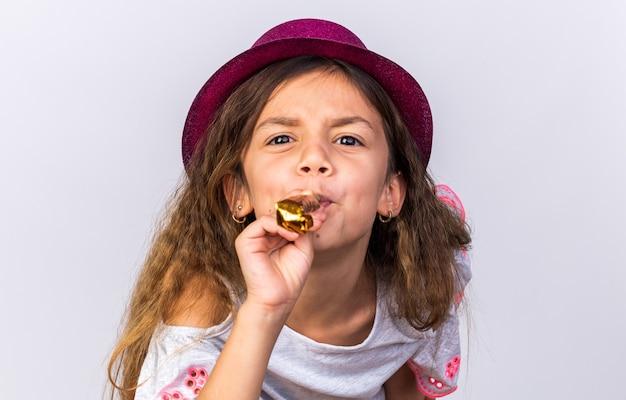 Раздраженная маленькая кавказская девушка с фиолетовой шляпой дует свисток и смотрит изолированно на белой стене с копией пространства