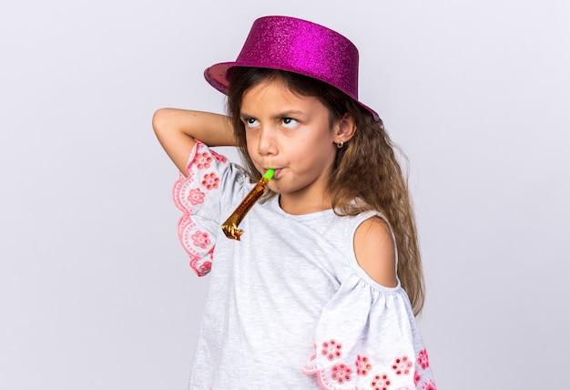 Раздраженная маленькая кавказская девушка с фиолетовой шляпой дует свисток и смотрит вверх изолированно на белой стене с копией пространства