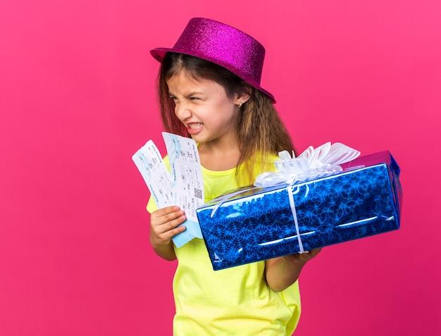 Infastidita piccola ragazza caucasica con cappello da festa viola che tiene in mano una confezione regalo e biglietti aerei guardando il lato isolato sulla parete rosa con spazio per la copia