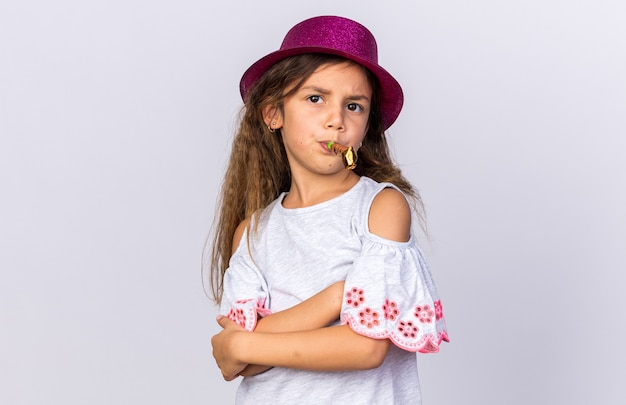 Annoyed little caucasian girl with purple party hat standing with crossed arms blowing party whistle isolated on white wall with copy space