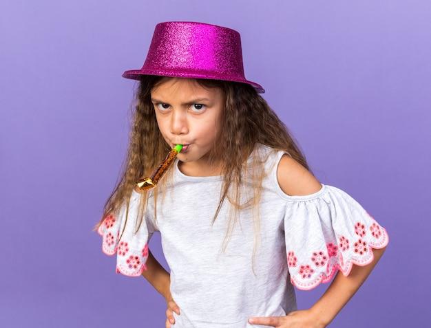 Раздраженная маленькая кавказская девушка с фиолетовой шляпой дует свисток на фиолетовой стене с копией пространства