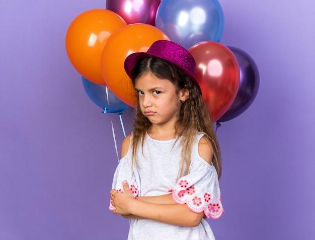 Раздраженная маленькая кавказская девушка в фиолетовой шляпе, стоящая со скрещенными руками перед гелиевыми шарами, изолированными на фиолетовой стене с копией пространства