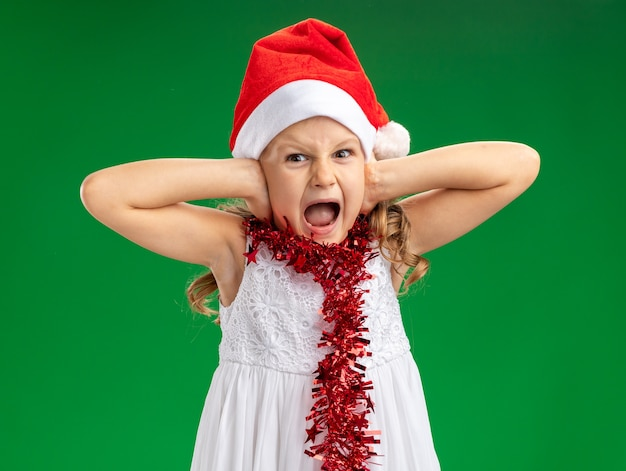 Annoyed little girl wearing christmas hat with garland on neck covered ears isolated on green background