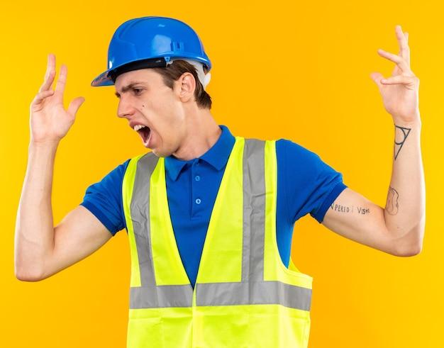 Un giovane costruttore di lato dall'aspetto infastidito in uniforme che allarga le mani