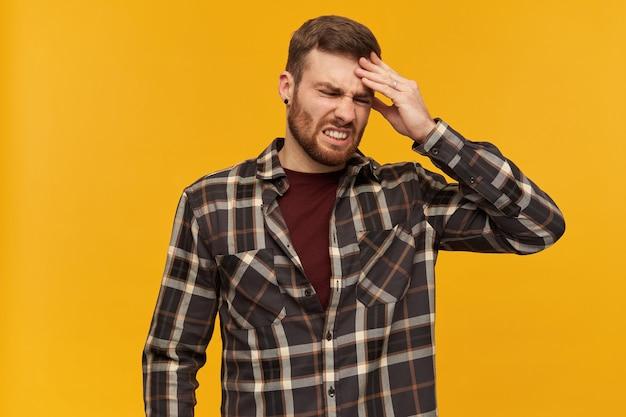 짜증이 난 남성, 갈색 머리와 수염을 가진 불쾌한 남자. 체크 무늬 셔츠와 액세서리 착용. 감정 개념. 그의 머리를 만지고. 두통으로 고통받습니다. 노란색 벽 위에 절연 스탠드